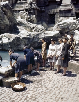 Italian women wash clothes at the fountain of Fontana Verdi while U.S. Army nurses and GI's look on. June 1944.