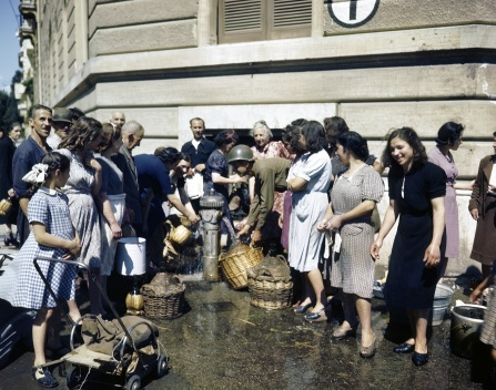 Pfc. Russell (Rock) Hebert of Beaumont, Texas, helps Italian women and children draw water from a hydrant. Americans estabilished water points for the Italian people because the Germans in northern Italy had control of the water supply. June, 1944.