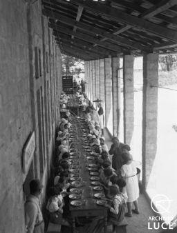 """Archivio Luce, Reparto Attualità, servizio fotografico n. 611 del 23.07.1930, """"Bambini della colonia montana """"Luigi Andena"""" di Monteluco, ripresi dall'alto, seduti lungo una tavolata, durante la pausa pranzo"""""""
