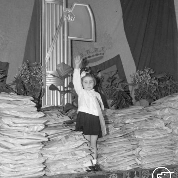 """Archivio Luce, Reparto Attualità, servizio fotografico n. 10 del 06.01.1939, """"Figlia della lupa, in piedi su un tavolo straripante di pacchi dono, mentre alza il braccio nel saluto fascista in occasione della Befana fascista organizzata al sanatorio Forlanini"""""""