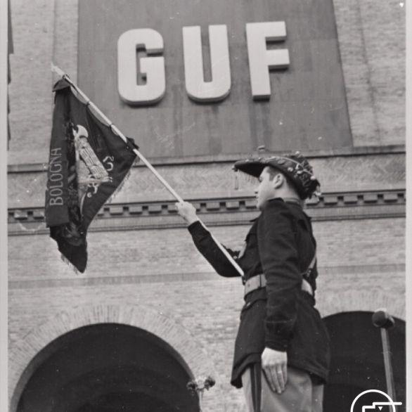 """Archivio Luce, Reparto Attualità, servizio fotografico n. 195 del 27.04.1940, """"Un giovane fascista universitario sta in piedi sul podio con la bandiera dei GUF di Bologna"""""""