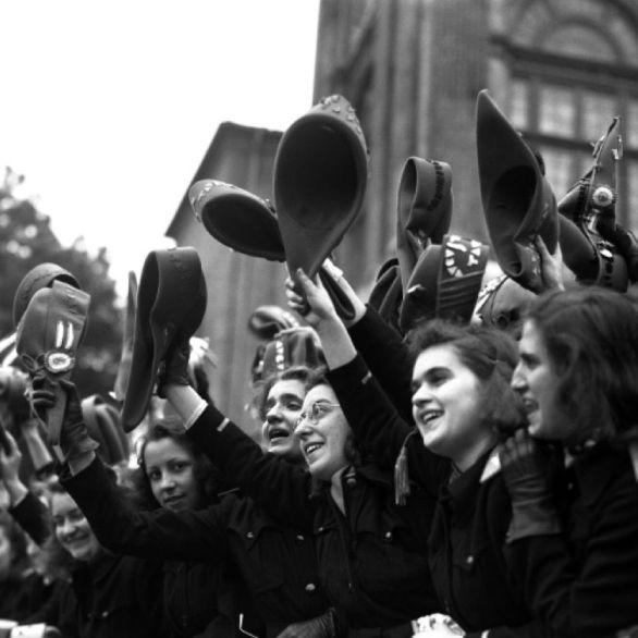 """Archivio Luce, Reparto Attualità, servizio fotografico n. 201 del 25.05.1942 - 27.05.1942, """"Un gruppo di studentesse universitarie saluta festosamente la parata della Divisione Tridentina"""""""